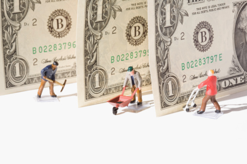 Figurines of manual workers with US dollar bills